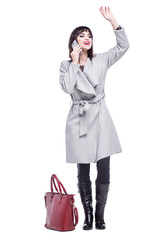 Beautiful woman dressed in a gray coat waving talking on the phone