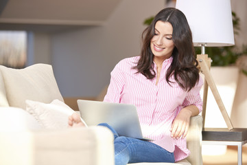Enjoying online time. Shot of young woman using her laptop at while sitting on cozy sofa.