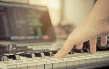 Muscian hand touching Keyboardin home studio