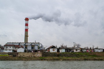 Factory polluting the city, releasing white gas, besite houses, down by the river