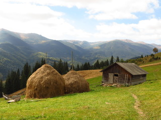 Old wooden hut and haystacks on  background of  beautiful mountain landscape and clouds.