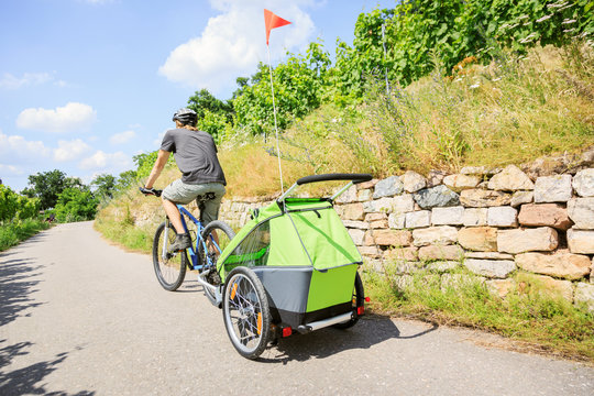 Young Parent Cycling With Bike Trailer