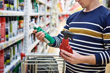 Man chooses spray for polishing car in supermarket