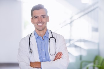 Portrait of smiling doctor standing with arms crossed