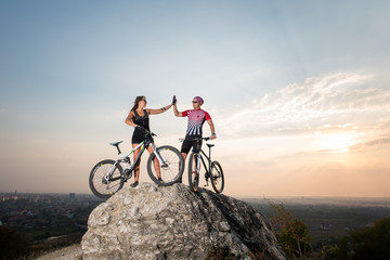 Man give high five for woman standing with the mountain bicycles on the rock under blue sky. Below is a small city in the distance
