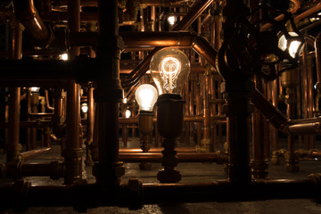 Incandescent light bulb between rusty pipes