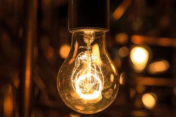 Incandescent light bulb between rusty pipes