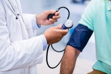Mid section of doctor checking blood pressure of a patient