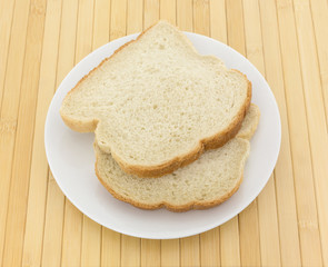 English muffin toasting bread slices on a white plate atop a wood place mat.