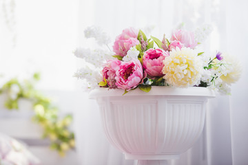 Pink and white flowers in a vase near the bed