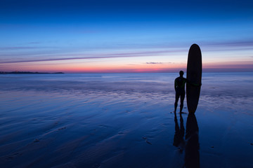 Silhouette of surfer on beach at sunset holding surfboard