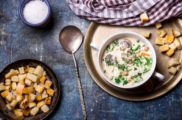 Cheese soup with croutons in white bowl.