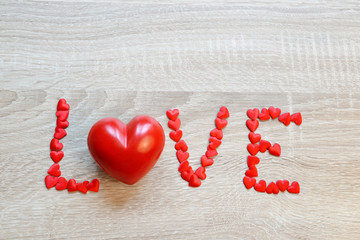 Text Love from the red hearts on wooden board.