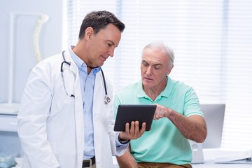 Doctor and senior patient using digital tablet