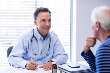 Doctor prescribing medicine to senior patient