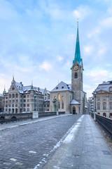 Winter landscape of Zurich. Waldmann monument and Munsterbrucke bridge, Switzerland