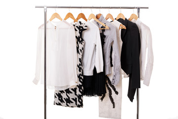 black and white womens clothes on hangers on rack on white backg