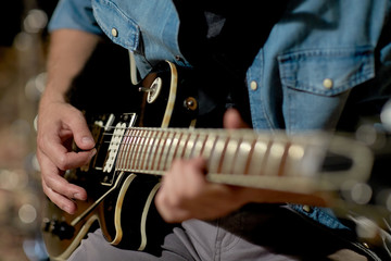 close up of man playing guitar at studio rehearsal