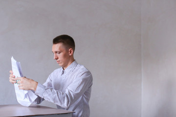 Successful young male worker stacks of paper and works in office