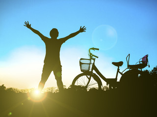 Silhouette of freedom man and bicycle on sunset background