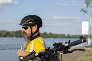 Cyclist taking a rest on a bench near river