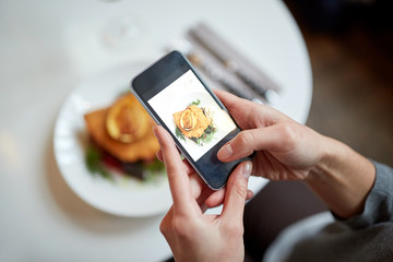 woman with smartphone photographing food at cafe