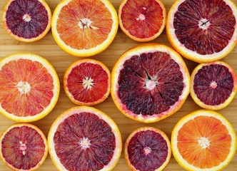 Tray of ruby red blood oranges cut in half