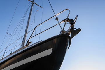 Bow of a black sailing yacht from below against the blue sky, copy space