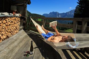 Mann liest in der Hängematte im Gebirge
