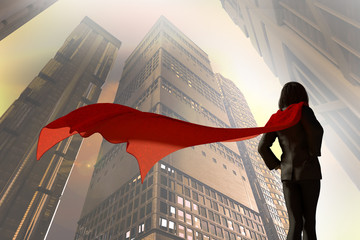3D Illustration of business woman dressed in a suit with a Cape superhero on the background of skyscrapers of the city