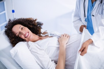 Doctor putting blanket on pregnant woman