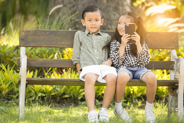 Little boy and girl enjoy taking photo by smartphone