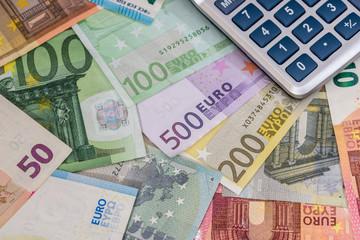 calculator above euro banknotes.