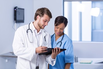 Doctors having discussion on clipboard