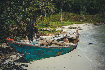Abandoned wooden boat on the sea shore.