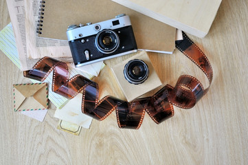 Old camera, film and lens on wooden background.