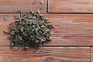 Heap of dry tea on brown wooden table