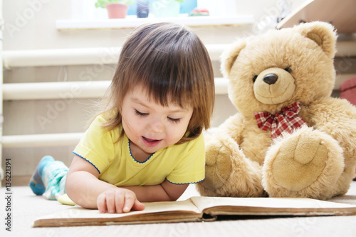 little girl reading book lying on stomach in her room on carpet with toy Teddy bear, smiling cute child, children education and development, happy childhood