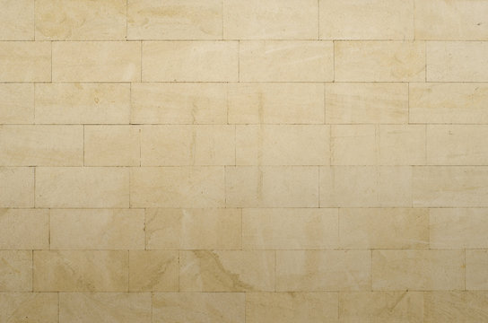 Background of gray-yellow porous sandstone blocks