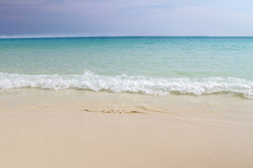 Beach and wave of blue ocean on sand summer background