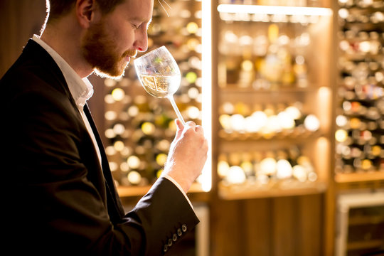 Young man tasting white wine