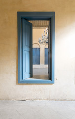 Opened blue wooden window with vintage plaster wall