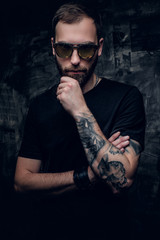 A man in sunglasses with tattoo on his arm.