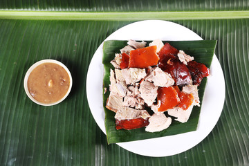 Chopped parts of the delicacy lechon or suckling pig on a banana leaf. The food is popular in Span and former Spanish colonial regions especially during fiesta