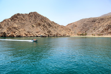Speedboat passing by a empty uninhabited small beach in Oman