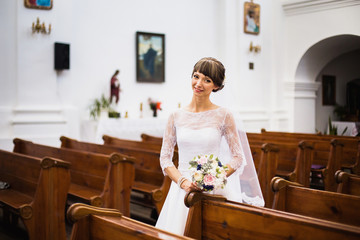 Beautiful bride in a white dress with a bouquet in the hands of the church. Wedding ceremony.