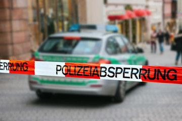 "Police tape in Germany at the crime scene with the inscription in German ""police cordon."" Focus on the police tape. In the background is a police car. Law, safety and security."