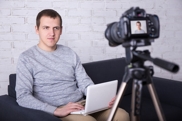 young man video blogger recording new video at home