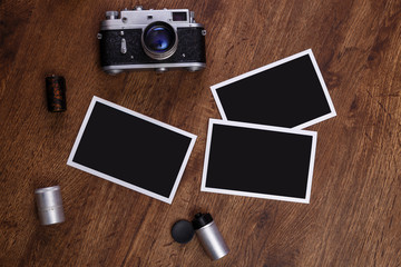 Vintage photo camera. Blank photo frames. Old aged camera rolls. Wooden rustic background.