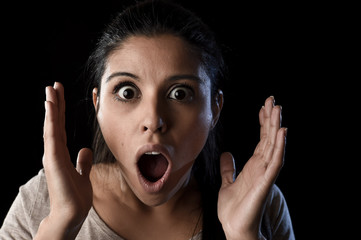 young beautiful scared Spanish woman in shock and surprise face expression isolated on black